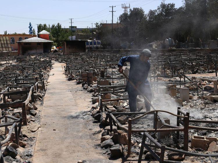 A man shovels debris after the Taliban burned a market in Ghazni