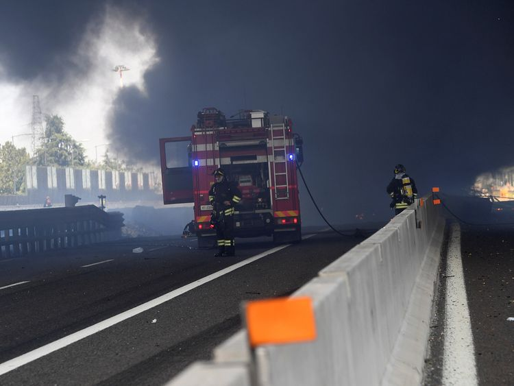 Firefighters work on the motorway after the accident
