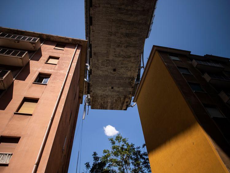 Apartment buildings are seen under the Morandi motorway bridge