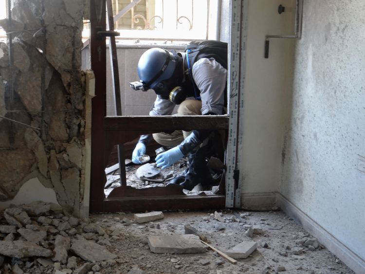 A UN arms expert collects samples in Ghouta during the investigation into the chemical weapons strike