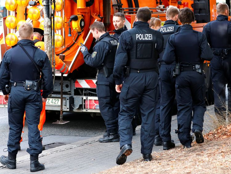 Police officers check street gullies close to the crime scene where a German man was stabbed in Chemnitz, Germany