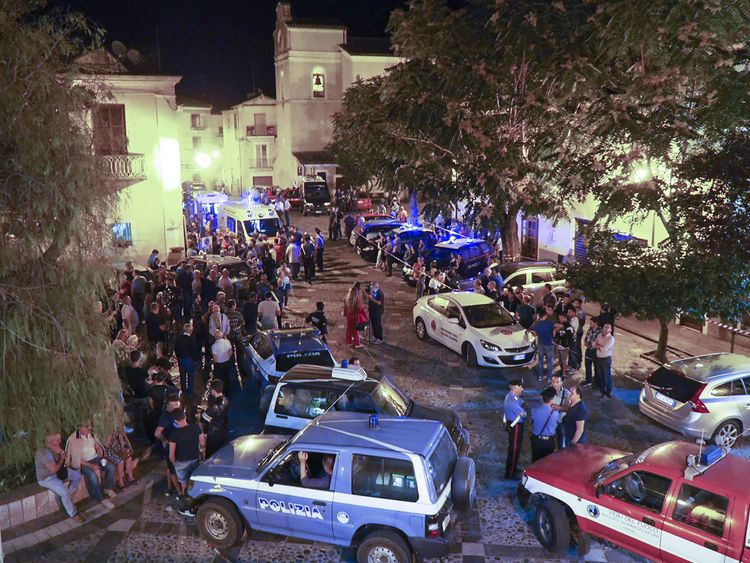 Rescuers and citizens await news at the central square in Civita, Calabria after flash floods killed 11