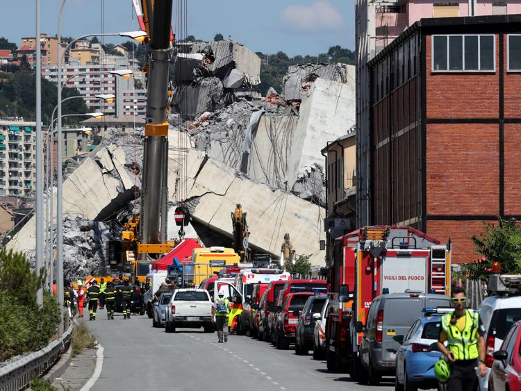 Firefighters and rescue workers stand at the site of the collapsed Morandi Bridge