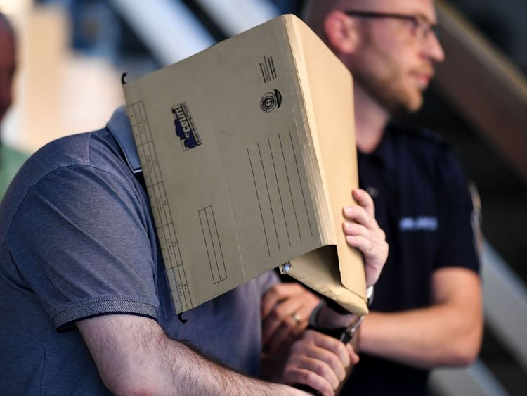 The Spanish defendant covers his face as he arrives in the courtroom in Freiburg, southern Germany, on August 6, 2018. - A German court jailed the Spanish man for 10 years for repeatedly sexually abusing a young boy whose mother and stepfather sold him to paedophiles online. (Photo by Patrick Seeger / dpa / AFP) / Germany OUT (Photo credit should read PATRICK SEEGER/AFP/Getty Images)