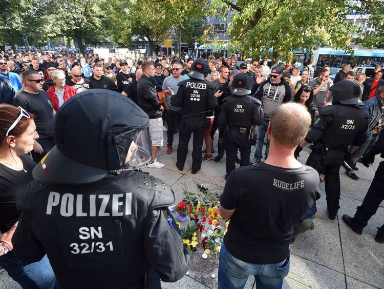 Riot police and citizens stand next to a makeshift memorial for a man who was stabbed to death