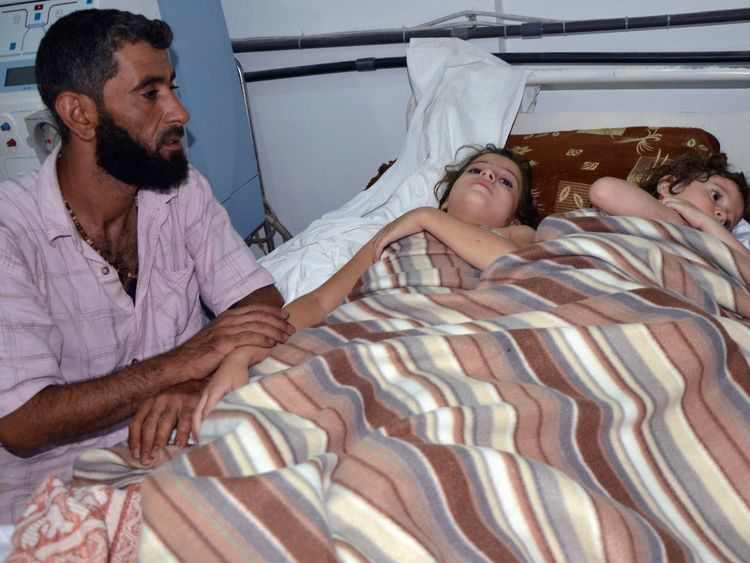 A man sits in a hospital near two children who are believed to have been affected by nerve gas in the 2013 attack in Ghouta