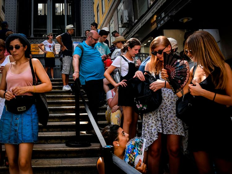 Tourists use fans as they queue to get on Santa Justa lift in downtown Lisbon