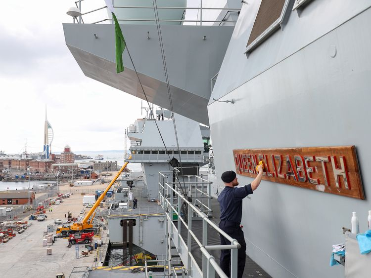 Able Seaman Ryan Whatmore, polishes the name board of HMS Queen Elizabeth, as final preparations are made prior to her setting sail for the US to undergo flight trials with the F35B for the first time