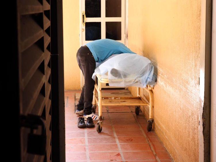 A young man bent over his dead relative sobbing
