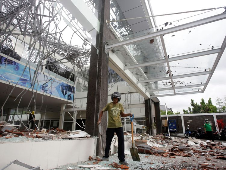 A man works in the damage a showroom car building after an earthquake in Bali, Indonesia
