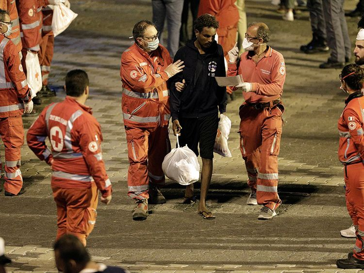 A migrant is helped by Red Cross members after disembarking the Italian coast guard ship