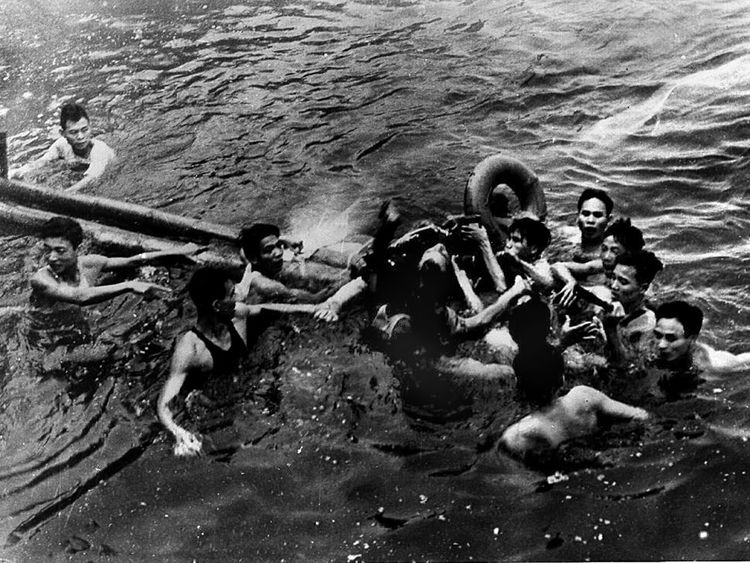 John McCain (C) being pulled from a lake in Hanoi after his Navy warplane was downed
