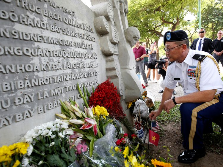 Military Attache Ton Tuan from US Embassy places incense at the McCain Memorial in Hanoi.
