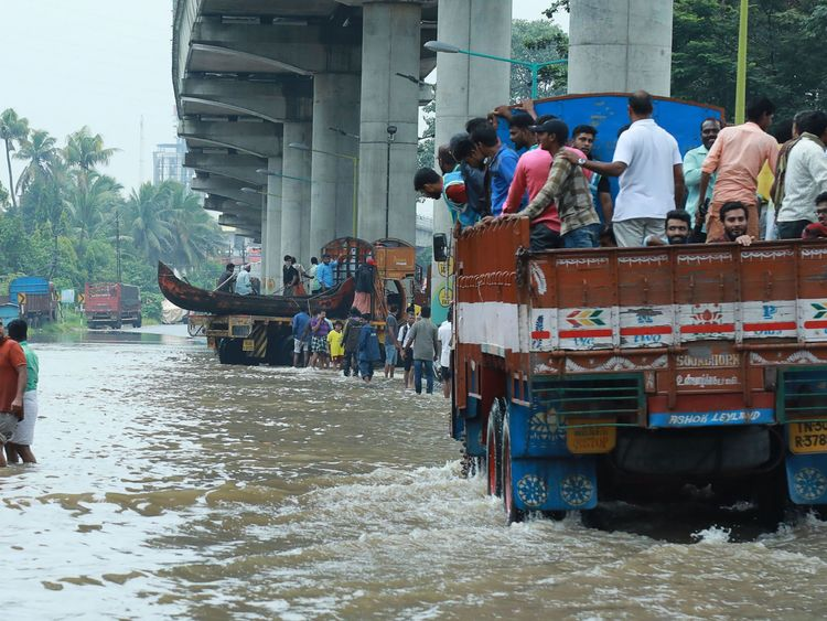 Indian commuters travel in a truck to a safer place as flood waters ravaged the National Highway 47 in Ernakulam district of Kochi, in the Indian state of Kerala