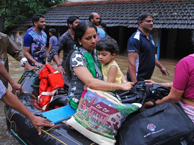 Indian volunteers and rescue personnel evacuate local residents in a boat in a residential area at Kozhikode, in the Indian state of Kerala