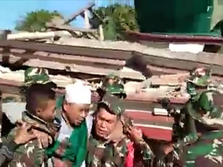 Indonesian soldiers on Monday rescued a man who was trapped beneath the rubble of a mosque which collapsed during a powerful quake