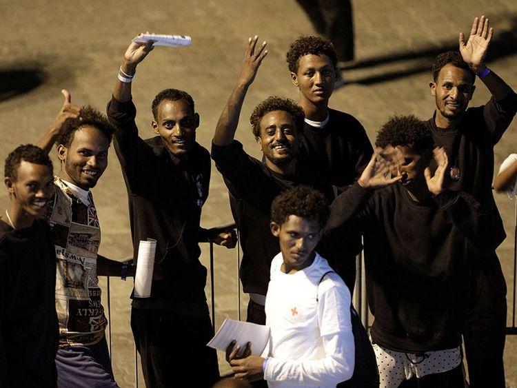 Migrants wave after disembarking from Italian coast guard vessel Diciotti at the port of Catania