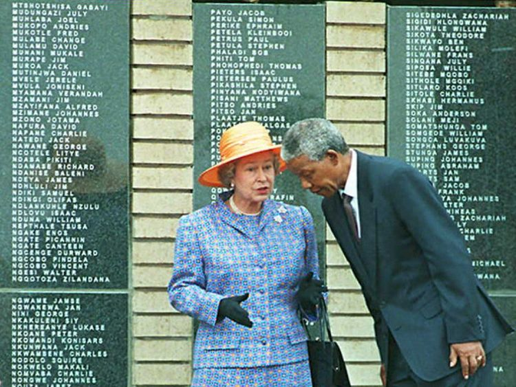 SOWETO, SOUTH AFRICA - MARCH 23: President Nelson Mandela leans forward as he speaks with Queen Elizabeth II at Avalon cemetery in Soweto, outside Johannesburg 23 March. The Queen unveiled a memorial to commemorate, 600 black soldiers who died when the SS-Mendi sank in the English Channel during World War I , in 1917. (COLOR KEY: Mandela wears dark blue suit). AFP PHOTO (Photo credit should read WALTER DHLADHLA/AFP/Getty Images)