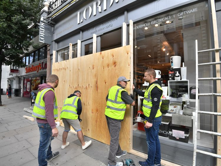 A shopfront being boarded up ahead of the bank holiday carnival