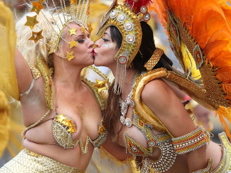 Performers in costume kiss as they take part in the carnival on the main Parade day of the Notting Hill Carnival in west London on August 27, 2018. - Nearly one million people are expected by the organizers Sunday and Monday in the streets of west London's Notting Hill to celebrate Caribbean culture at a carnival considered the largest street demonstration in Europe. (Photo by Daniel LEAL-OLIVAS / AFP) (Photo credit should read DANIEL LEAL-OLIVAS/AFP/Getty Images)