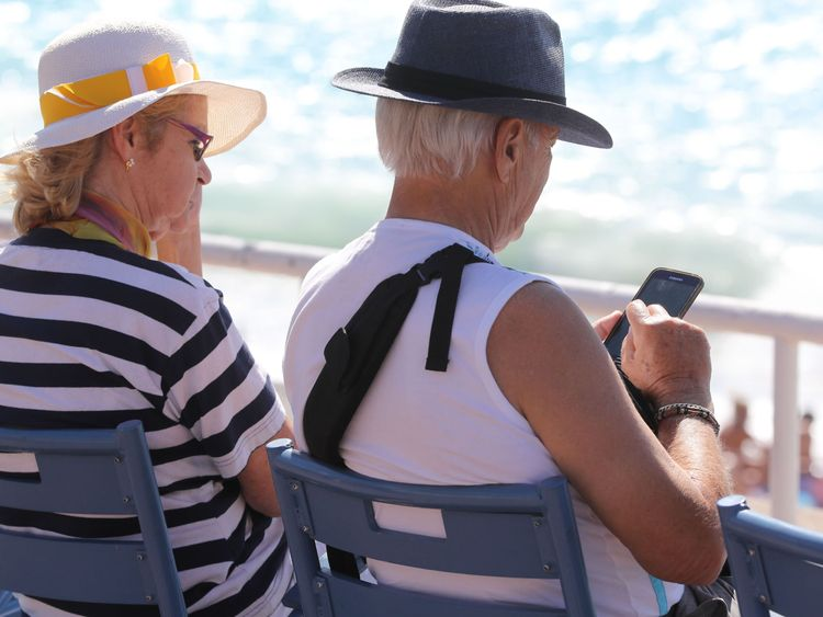 An elderly man uses a mobile phone while sitting on the Promenades des Anglais beachfront in the French riviera city of Nice on September 1, 2017. In a largely saturated telecommunications market, there is still a large share of the population that remains under-equipped and offers growth prospects: senior citizens. / AFP PHOTO / VALERY HACHE (Photo credit should read VALERY HACHE/AFP/Getty Images)