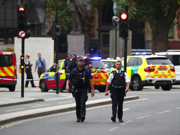 Police patrol the scene outside parliament where a car is said to have crashed