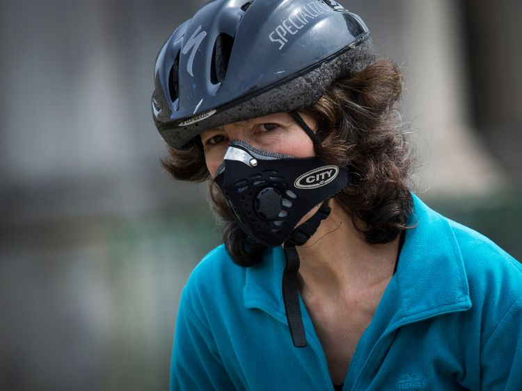 A female cyclist in London wears a protective mask to avoid breathing in toxic air