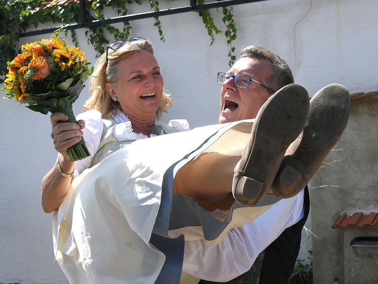 Wolfgang Meilinger prepares to carry his bride over the threshold