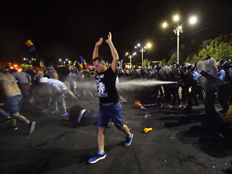 Protesters flee as riot police fire tear gas
