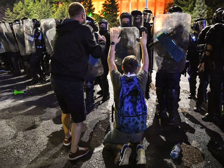 Protesters sit and stand in front of riot police