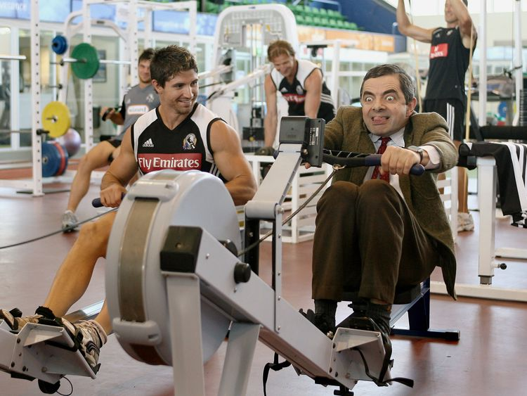 British actor and comedian Rowan Atkinson (R), in character as 'Mr Bean', competes with footballer Brodie Holland (L) on a rowing machine as he visits the Collingwood Football Club - Australia's best known Aussie Rules team, in Melbourne 09 March 2007. Atkinson is in Melbourne to promote his new movie 'Mr Bean's Holiday'. AFP PHOTO/William WEST (Photo credit should read WILLIAM WEST/AFP/Getty Images)