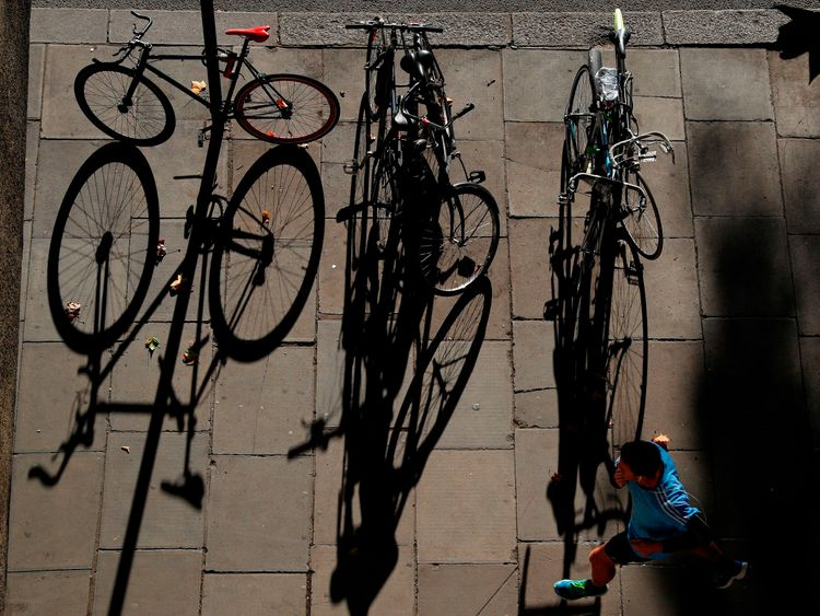 A jogger passes the shadows of bicycles as he runs along the Embankment, pictured from Waterloo Bridge in central London on November 6, 2017. / AFP PHOTO / Adrian DENNIS (Photo credit should read ADRIAN DENNIS/AFP/Getty Images)