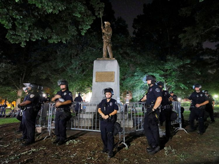 Police wearing riot gear guard a statue of a Confederate soldier nicknamed Silent Sam on the campus of the University of North Carolina during a demonstration for its removal in Chapel Hill, North Carolina, U.S. August 22, 2017. REUTERS/Jonathan Drake TPX IMAGES OF THE DAY