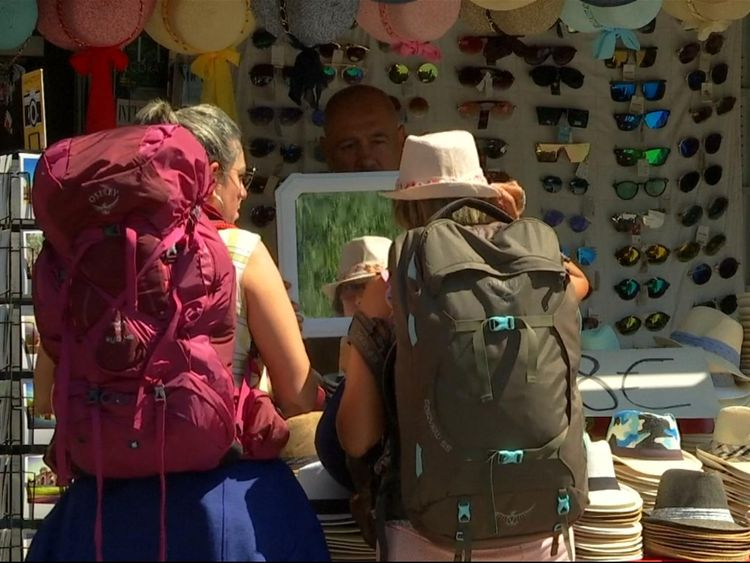 Two backpackers stop to buy hats in Madrid