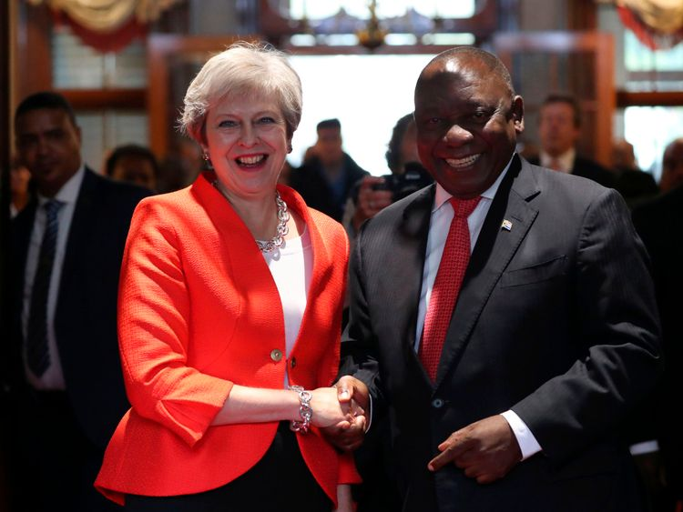 Britain's Prime Minister Theresa May is greeted by South African President Cyril Ramaphosa in Cape Town