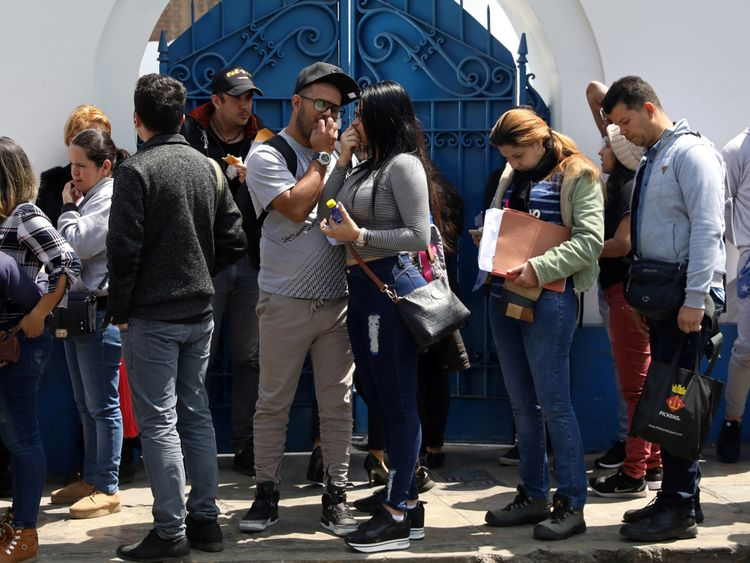Venezuelan migrants queue outside the immigration office in Lima, Peru