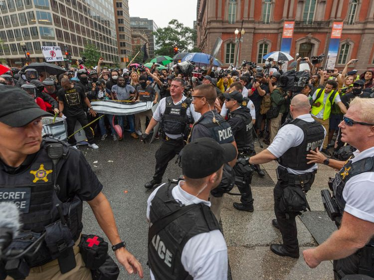 Metro Police and Secret Service personnel are forced back by counter-protesters outside of the Pennsylvania Avenue security barrier