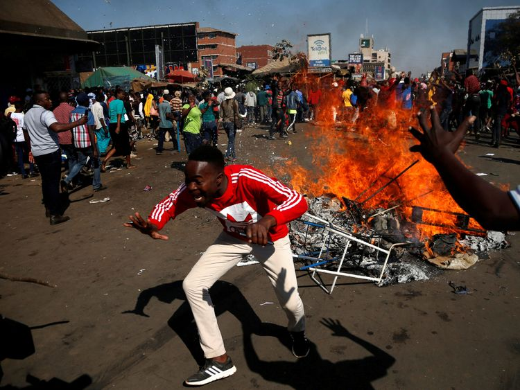 Supporters of the opposition Movement for Democratic Change party (MDC) of Nelson Chamisa block a street in Harare, Zimbabwe