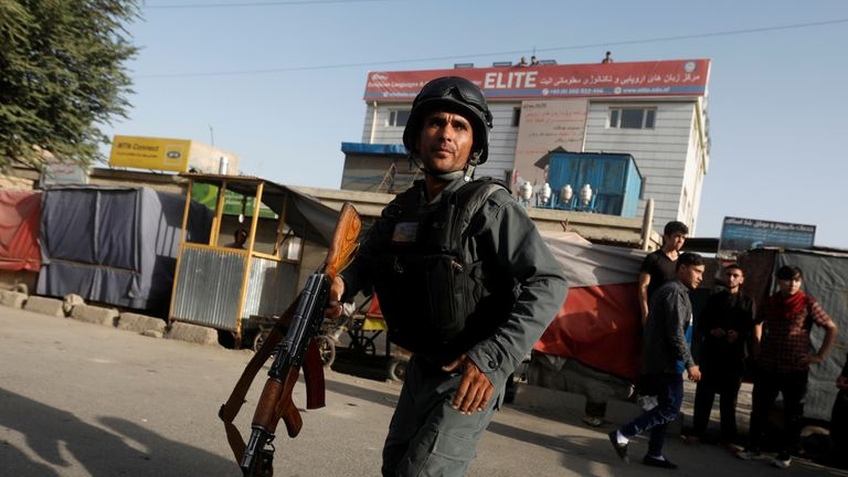Afghan policemen arrive at the site of the bomb blast in Kabul