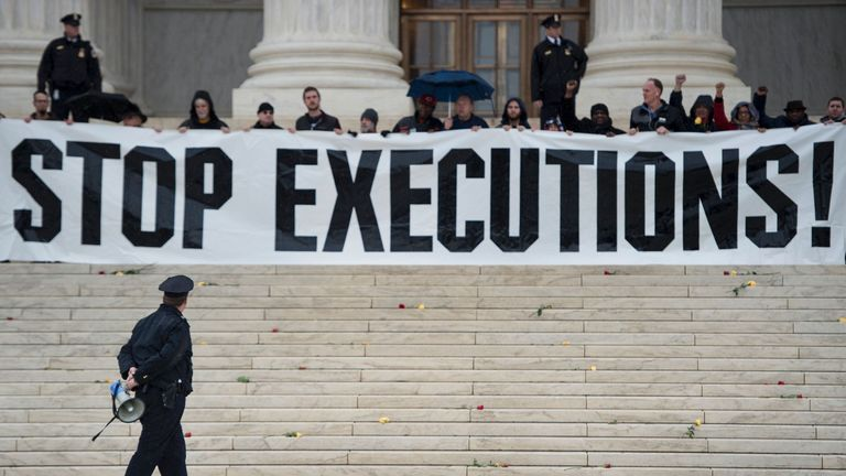 A police officer warns activists to leave during an anti-death penalty protest in front of the US Supreme Court