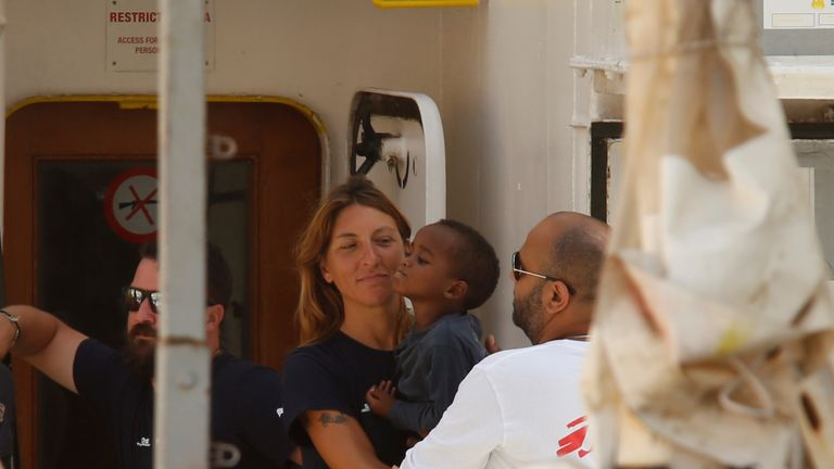 A child is held by a rescue worker on the Aquarius
