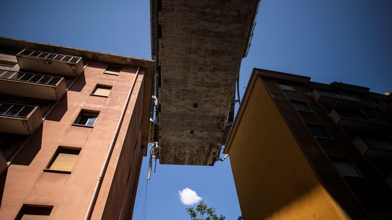 Apartment buildings are seen under the Morandi motorway bridge