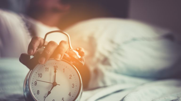 Clock on the bed in the morning.
