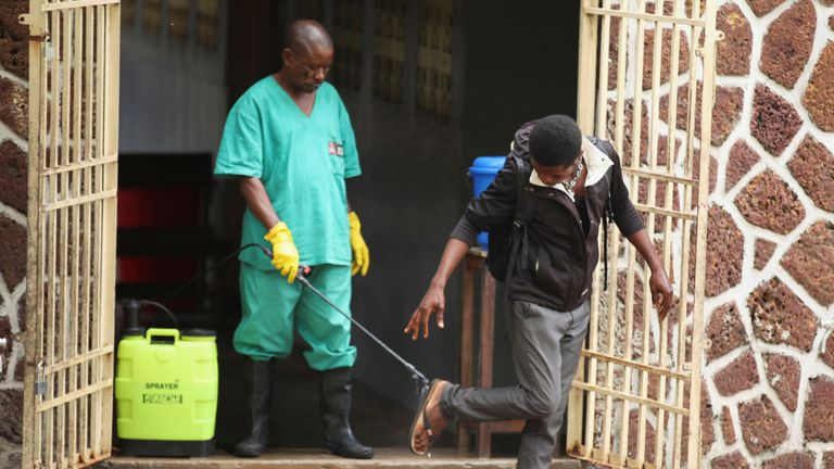 A health worker sprays a visitor with chlorine after leaving the isolation facility, prepared to receive suspected Ebola cases, at the Mbandaka General Hospital, in Mbandaka, Democratic Republic of Congo May 20, 2018