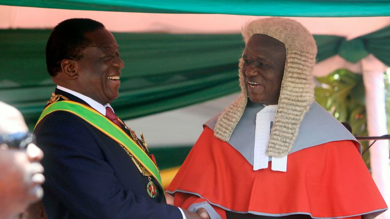 "Zimbabwean President Emmerson Mnangagwa,left, is congratulated by Chief Justice Luke Malaba after taking his oath during his inauguration ceremony at the National Sports Stadium in Harare, Sunday, Aug. 26, 2018. The Constitutional Court upheld Mnangagwa's narrow election win Friday, saying the opposition did not provide "" sufficient and credible evidence"" to back vote- rigging claims.(AP Photo/Tsvangirayi Mukwazhi)"