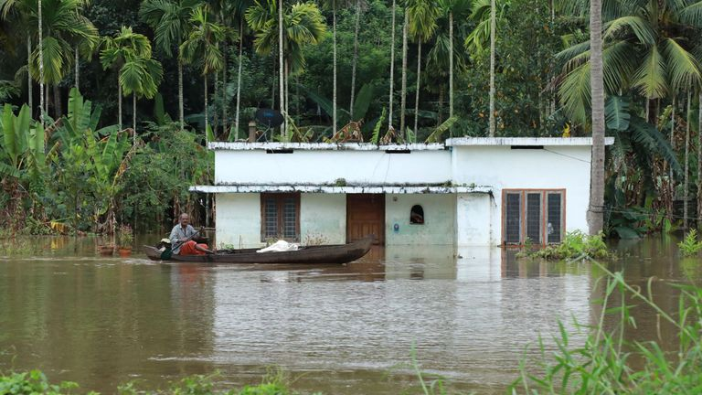 An Indian man rides his boat next to houses immersed in flood waters in Ernakulam district of Kochi, in the Indian state of Kerala