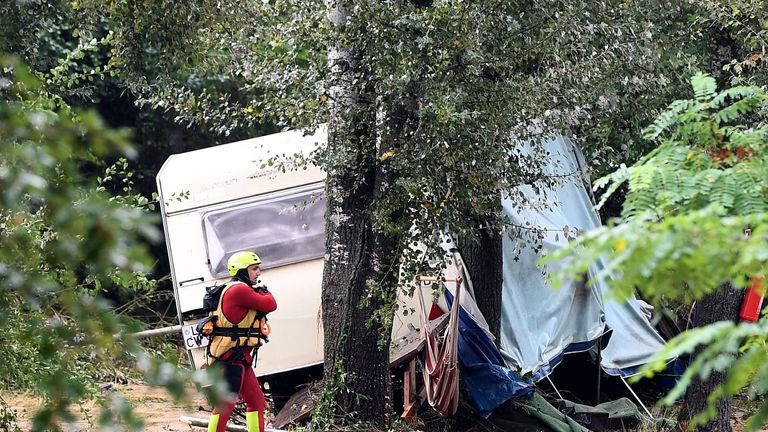 A rescuer walks in front of a damaged caravan in southern France