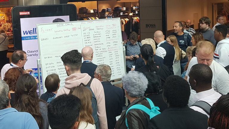 Passengers gather around a whiteboard with the information
