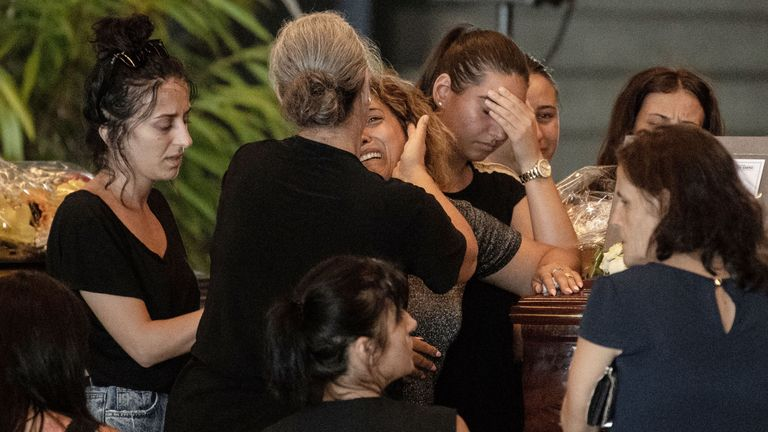 Relatives pray and pay their respects near the coffin of a victim of the Morandi bridge's collapse, in Genoa, on August 17, 2018. - Italy prepares to pay homage to the victims of the deadly bridge collapse as rescuers use diggers to claw through mountains of rubble in a desperate search for survivors, but some families are reportedly refusing the join the state memorial ceremony. A vast span of the Morandi bridge caved in during a heavy rainstorm in the northern port city of Genoa on August 14,