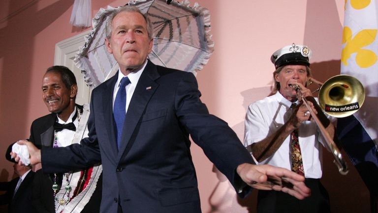 US President George W. Bush (C) dances with the Burnell Brunious (L), grand marshal of the Euphonious brass dixie band, during a United States Chamber of Commerce Reception at Gallier Hall in New Orleans, Louisiana, on April 21, 2008. AFP PHOTO/SAUL LOEB (Photo credit should read SAUL LOEB/AFP/Getty Images)